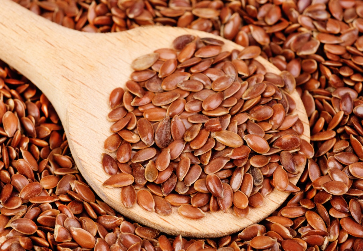 close up of flax seeds and  wooden spoon food background