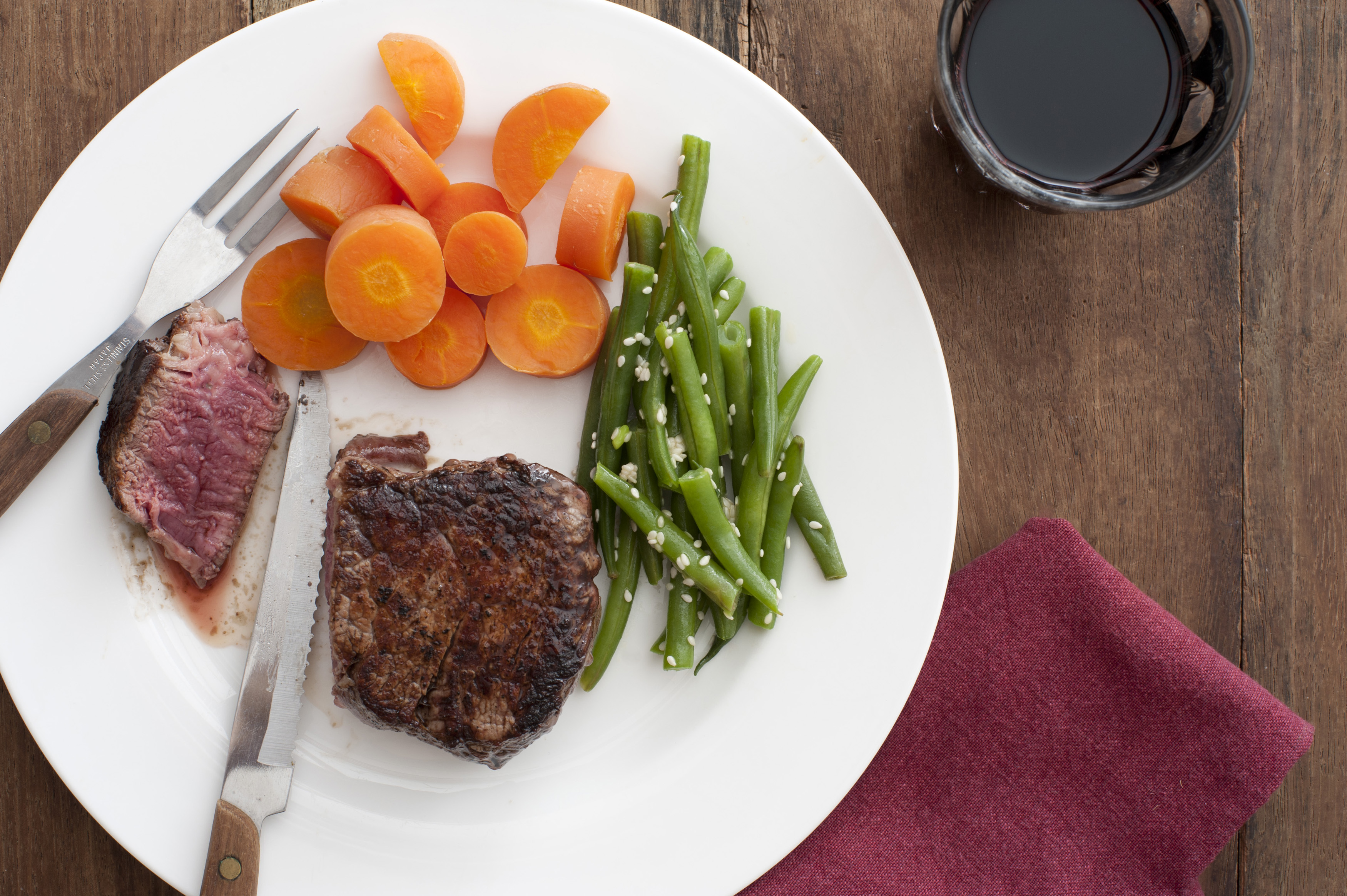 Steak meal with fresh steamed vegetables, carrots and fresh green string or runner beans, viewed high angle with the steak cut through to show the tender juicy meat