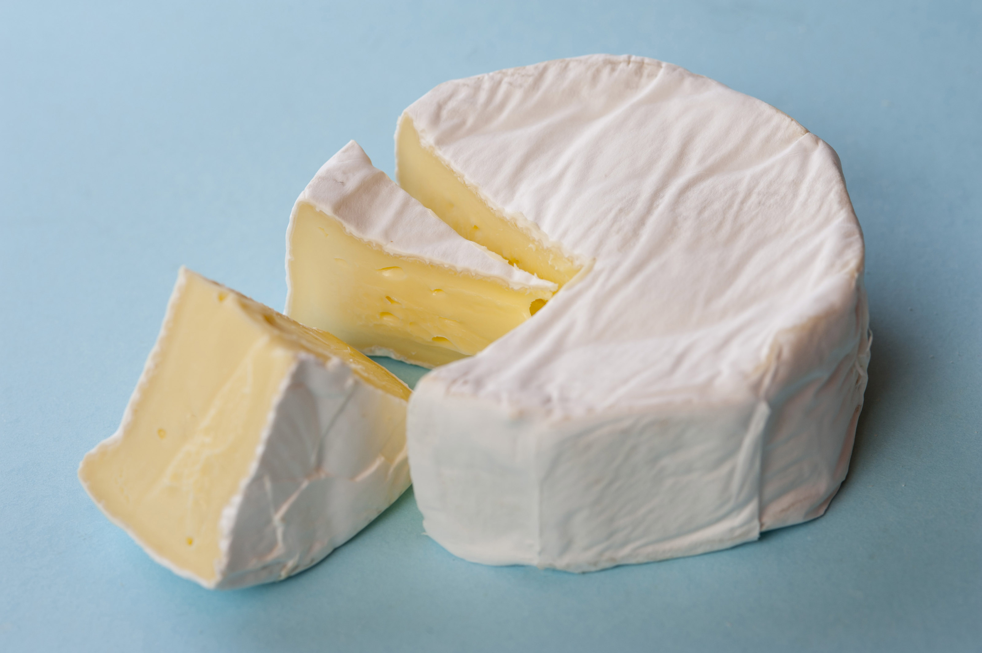 Round of mature soft brie cheese with two wedges removed to display the centre