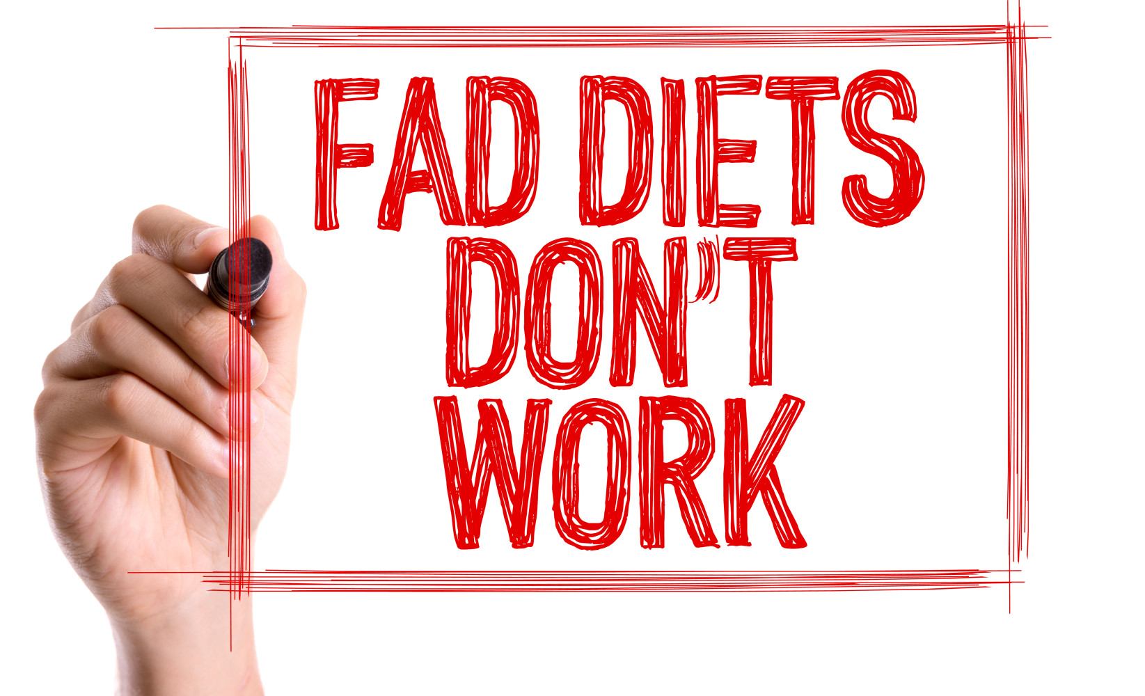 Hand with marker writing the word Fad Diets Don't Work