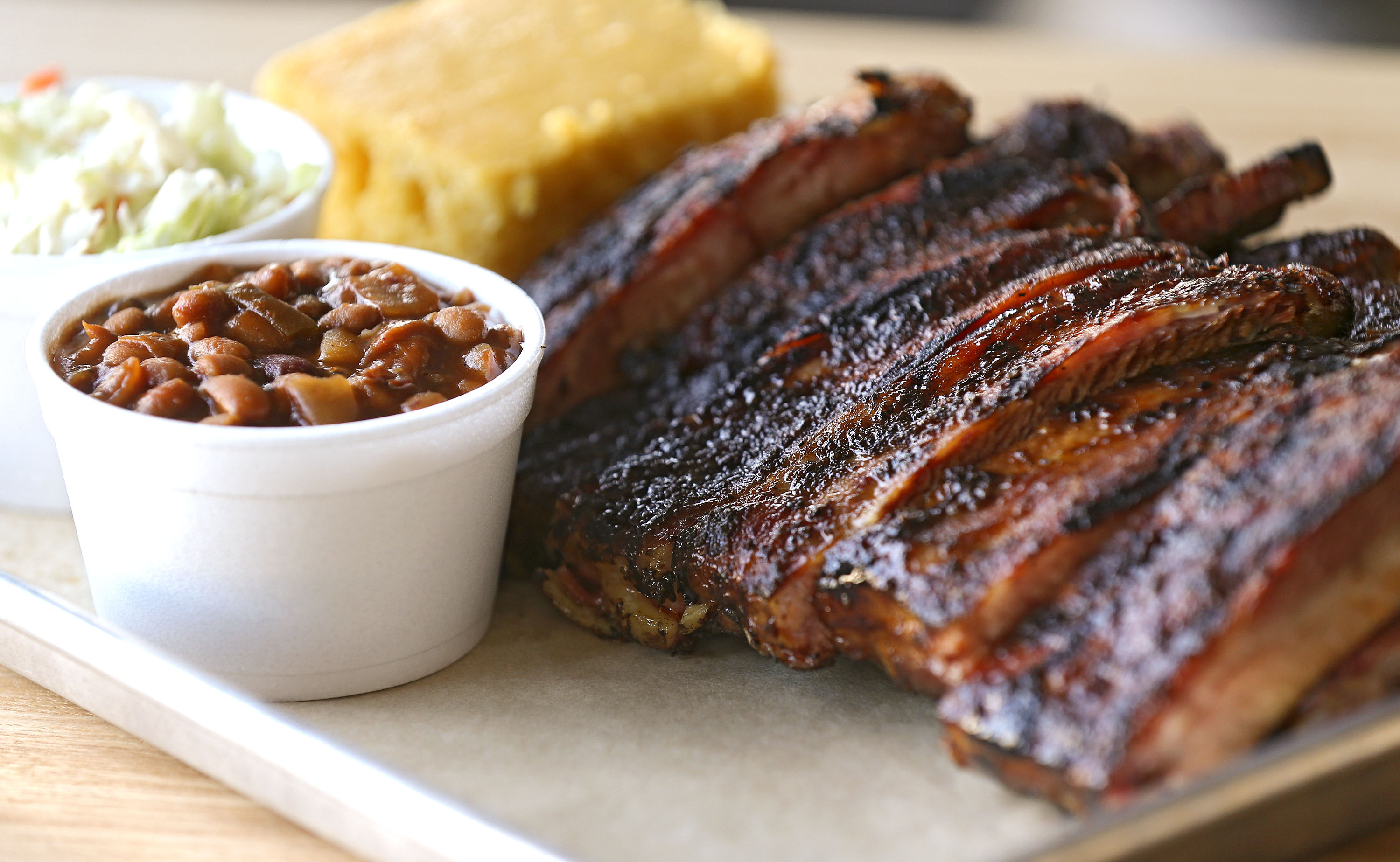 The Full Slab of Ribs meal with coleslaw and baked beans sides and a slice of honey butter corn bread at Jimmy Jack's Rib Shack in Iowa City on Thursday, Oct. 13, 2016. The ribs are St. Louis style pork ribs. (Stephen Mally/The Gazette)